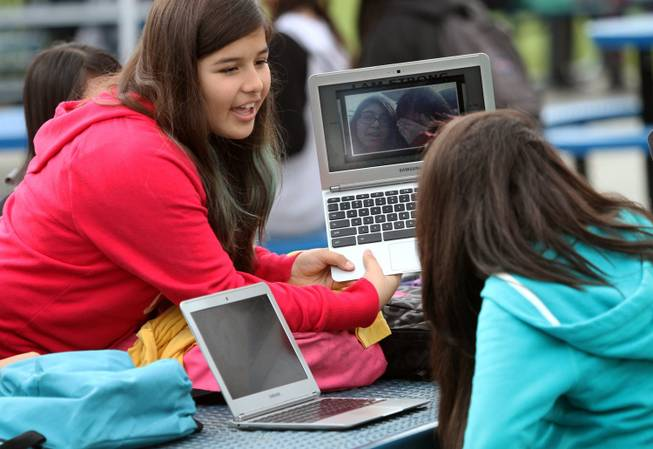 Pinacate Middle School student Melissa Lopez, 12, left, holds her Chromebook up so that Jasmin Cadenes, 12, can see it at their lunch table, Dec. 6, 2013, in Perris, Calif.