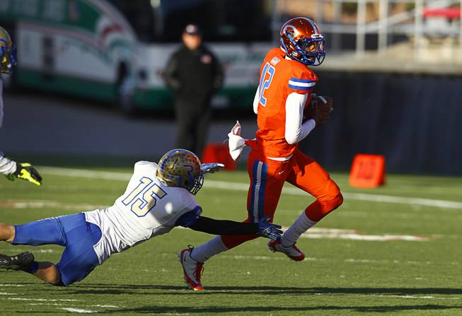 Bishop Gorman High School quarterback Randall Cunningham Jr. avoids Reed High School's Collin Palian (15) during their Division I state high school football championship game against Reed High School of Sparks, Nev. at Sam Boyd Stadium Saturday, Dec. 7, 2013.