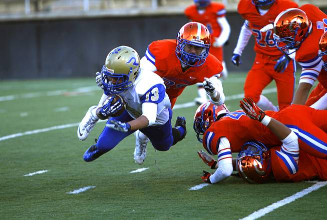 Reed High School wide receiver Jorden Carter (13) is tripped up by members of the Bishop Gorman defense during their Division I state high school football championship game at Sam Boyd Stadium Saturday, Dec. 7, 2013.