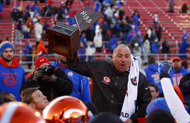 Bishop Gorman High School head football coach Tony Sanchez holds up the trophy  after Bishop Gorman beat Reed High School in the Division I state high school football championship game at Sam Boyd Stadium Saturday, Dec. 7, 2013.