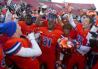 Bishop Gorman High School players celebrate after defeating Reed High School of Sparks, Nev. in the Division I state high school football championship game at Sam Boyd Stadium Saturday, Dec. 7, 2013.