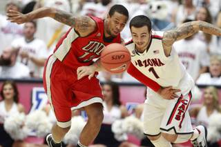 UNLV guard Bryce Dejan Jones steals the ball from Arizona guard Gabe York during the first half of their game at the McKale Center in Tucson Saturday, Dec. 7, 2013.