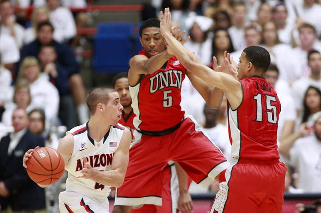 UNLV forward Chris Wood and guard Kendall Smith defend Arizona guard T.J. McConnell during their game at the McKale Center in Tucson Saturday, Dec. 7, 2013. Arizona won the game 63-58.