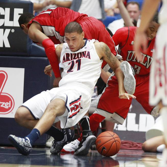 UNLV guard Bryce Dejean Jones and Arizona forward Brandon Ashley get tangled up during their game at the McKale Center in Tucson Saturday, Dec. 7, 2013. Arizona won the game 63-58.