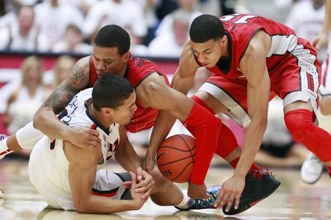 UNLV guards Bryce Dejean-Jones and Kendall Smith fight Arizona guard Nick Johnson for a loose ball during their game at the McKale Center in Tucson on Saturday, Dec. 7, 2013. Arizona won the game 63-58.
