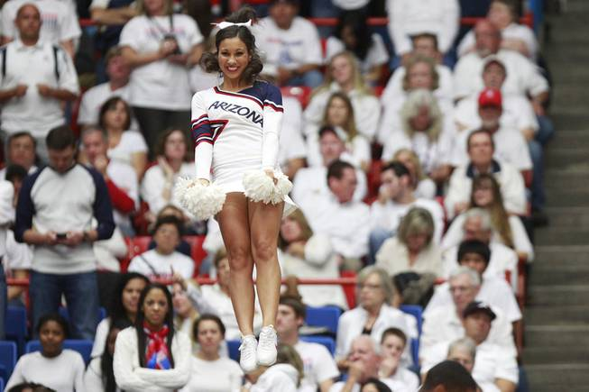 An Arizona cheerleader performs during their game against UNLV at the McKale Center in Tucson Saturday, Dec. 7, 2013. Arizona won the game 63-58.