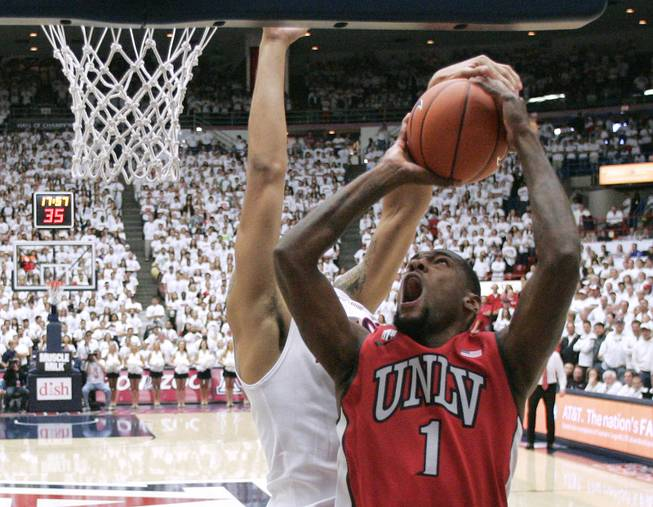 UNLV forward Roscoe Smith is fouled by Arizona while taking a shot during their game at the McKale Center in Tucson Saturday, Dec. 7, 2013. Arizona won the game 63-58.