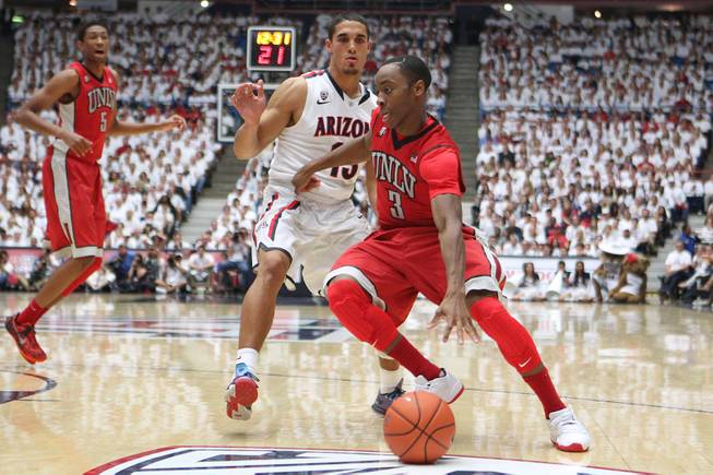 UNLV guard Kevin Olekaibe drives around Arizona guard Nick Johnson during their game at the McKale Center in Tucson Saturday, Dec. 7, 2013. Arizona won the game 63-58.
