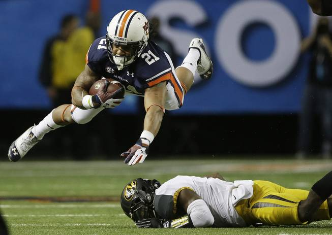 Auburn running back Tre Mason makes the catch and goes over Missouri defensive back John Gibson during the first half of the Southeastern Conference NCAA football championship game Saturday, Dec. 7, 2013, in Atlanta.