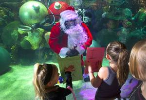 Olivia Krause, 4, and her sister Tori, of Elko, Nev. show their wish lists to Santa Claus at the Silverton Casino Hotel in Las Vegas, Nevada December 8, 2013. The underwater Santa and his helpers greet visitors and take present requests from inside the casino's 117,000-gallon aquarium on weekends in December until Christmas.