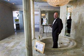 British businessman Martyn J. Ravenhill poses in a marble bath tub during an open house and book signing at the Liberace house Monday, Dec. 9, 2013. Ravenhill purchased Liberace's former residence for $500,000 in August. He also recently published a book titled