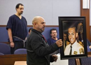 Ernesto Velasquez holds a picture of his son Angel as he addresses the court during sentencing for Jvon Williams on Monday,  Dec. 9, 2013.