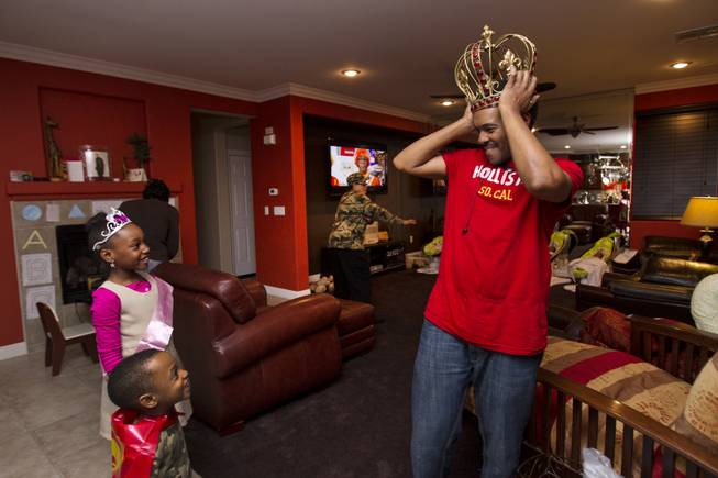 Deon Derrico shows off his giant crown to his daughter Darian, 8, and son Derrick, 3, as the family gathers to celebrate Darian's birthday Monday, Dec. 9, 2013.
