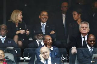 President Barack Obama jokes with Danish prime minister, Helle Thorning-Schmidt, left, as first lady Michelle Obama looks on at right during the memorial service for former South African president Nelson Mandela at the FNB Stadium in Soweto, near Johannesburg, South Africa, Tuesday Dec. 10, 2013.