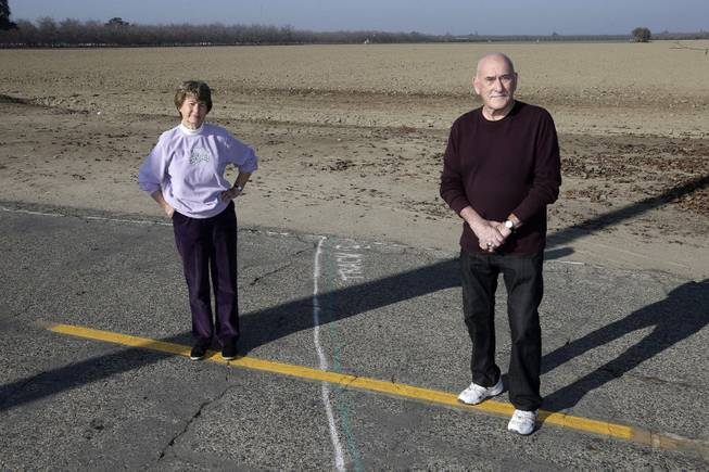 Phyllis and Ross Browning stand alongside a line drawn across Cairo Avenue marking the path of the proposed high-speed rail through their Hanford, Calif., neighborhood, Dec. 12, 2013. The proposed rail line will run a few houses away from their residence. The couple moved to Hanford in 2005 to retire and live next door to Phyllis' mother.