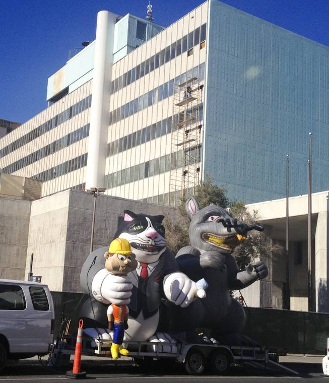 An inflated rat and cat holding a construction worker stand vigil at the old Clark County courthouse, 200 S. 3rd St Thursday, Dec. 12, 2013.