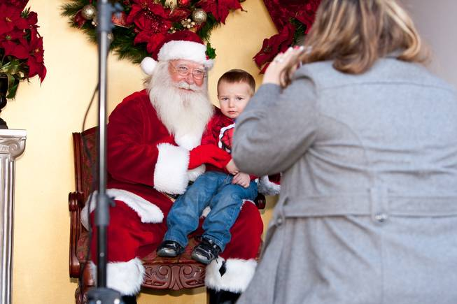 Landon Harrison, 2, looks a bit uneasy while his mom, Melissa, takes a photograph of him with Santa Claus in his cottage at Tivoli Village in Las Vegas Friday, December 13, 2013.  Larry Hansen has been donning the coveted suit and sharing the spirit of Santa for over nine years in Las Vegas.