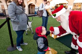 Landon Harrison, 2, gives Santa a high five after visiting him in his cottage at Tivoli Village in Las Vegas Friday, December 13, 2013.  Larry Hansen has been donning the coveted suit and sharing the spirit of Santa for over nine years in Las Vegas.