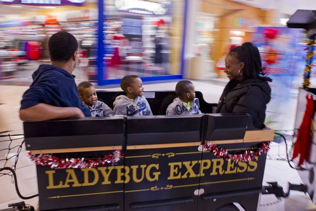 Deon and Evonne Derrico ride the Ladybug Express with their sons during a Christmas shopping trip to the mall Friday, Dec. 13, 2013.