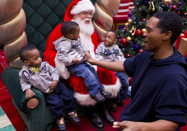Deon Derrico and his sons visit with Santa during a Christmas gift shopping trip to the mall Friday, Dec. 13, 2013.