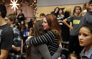 Freshman Allie Zadrow, center right, hugs classmate Liz Reinhardt at a church after a shooting at nearby Arapahoe High School in Centennial, Colo., on Friday, Dec. 13, 2013. Students from the school were evacuated to the church. Arapahoe County Sheriff Grayson Robinson said the shooter shot two others at the school before apparently killing himself.