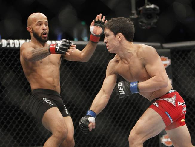Demetrious Johnson, left, avoids a punch from Joseph Benavidez in a UFC flyweight mixed martial arts title fight in Sacramento, Calif., Saturday, Dec. 14, 2013.