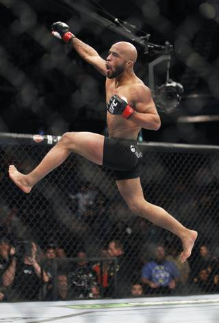 Defending champ Demetrious Johnson celebrates after knocking out Joseph Benavidez in the first round of their UFC flyweight mixed martial arts title fight in Sacramento, Calif., Saturday, Dec. 14, 2013.