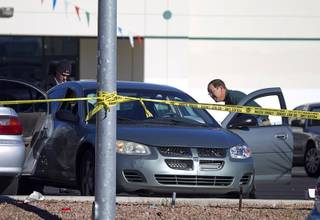 Metro Police detectives and crime scene analysts investigate a fatal shooting in front of a furniture store on Spring Mountain Road Sunday, Dec. 15, 2013.