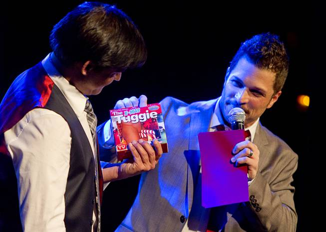 "Deven May receives a gift from Mark Shunock during ""Mondays Dark,"" a monthly charitable event, at Body English on Monday, Dec. 16, 2013, in the Hard Rock Hotel."