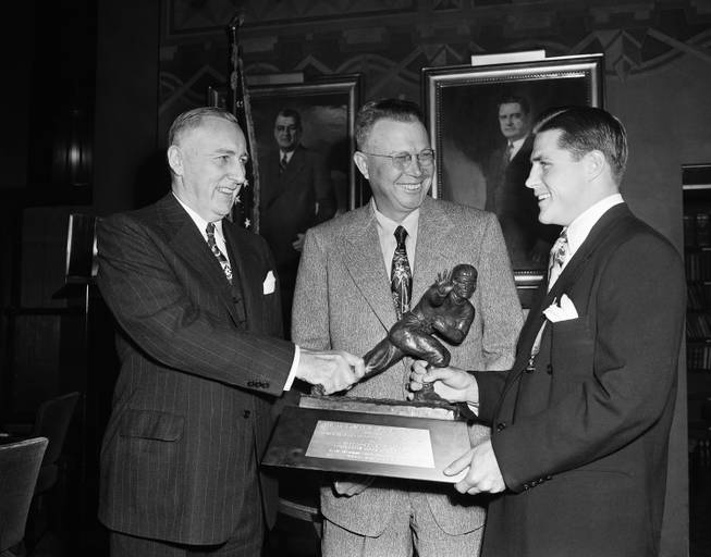 Doak Walker, a star player for Southern Methodist, looks over Heisman Memorial Trophy in New York on Dec. 7, 1948. Picked as the nation's outstanding college football player by sportswriters and broadcasters, Walker formally was presented with the award later in the day at a dinner in the Downtown Athletic Club.