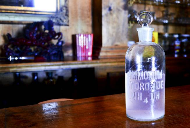 A bottle marked ammonium hydroxide, which was found on the grounds of the Belmont Inn and Saloon, sits on the bar. Believed to be from Belmont's early history, it was cleaned and filled with colored water.
