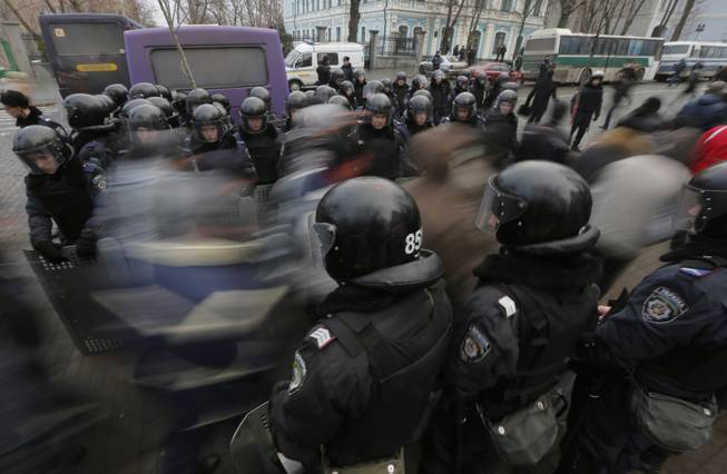 Pro-European Union activists pass through a police line as they march against the government in Kiev, Ukraine, Tuesday, Dec. 17, 2013. Weeks of angry pro-European Union protests as well as Western pressure have forced Yanukoyvch to make some concessions to the opposition. Last week Yanukovych called for an amnesty for some of the activists detained.