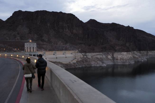 Visitors to Hoover Dam and Lake Mead walk near canyon walls ringed with white mineral deposits where water once lapped indicating the drop in water levels, near Boulder City, Nev., Dec. 18, 2013.