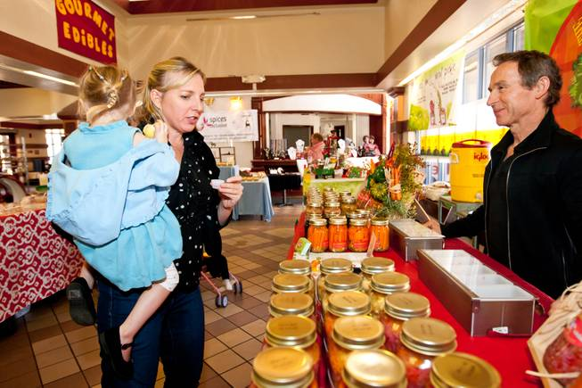 While shopping with her daughter, Clairin DeMartini describes the flavor of the sweet and spicy beets sampled in Nick Kreway's The Pickled Pantry booth at the Downtown Farmers' Market in Las Vegas Friday, December 20, 2013.