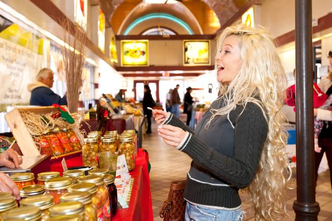 Bianca Paris reacts with surprise when the hot and spicy kick sets in while sampling pickled carrots in The Pickled Pantry booth at the Downtown Farmers' Market in Las Vegas Friday, December 20, 2013.