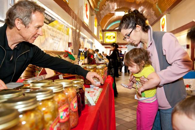 Nick Kreway offers pickled carrots to two-year-old Sophie Meza and her mom, Laura, while selling his pickled products from The Pickled Pantry booth at the Downtown Farmers' Market in Las Vegas Friday, December 20, 2013.