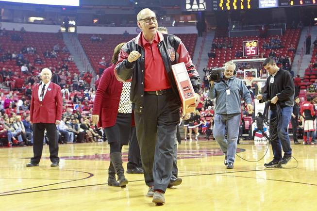 Outgoing UNLV President Neal Smatresk walks off the court after being honored during a timeout in their game against Sacred Heart Friday, Dec. 20, 2013 at the Thomas & Mack Center. UNLV won the game 82-50.