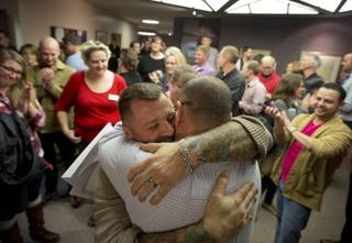 Chris Serrano, left, and Clifton Webb embrace after being married, as people wait in line to get licenses outside of the marriage division of the Salt Lake County Clerk's Office in Salt Lake City, Friday, Dec. 20, 2013. A federal judge ruled on Friday that Utah's ban on same-sex marriage is unconstitutional. (AP Photo/Kim Raff)