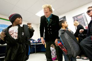 Kenneth Williams, left, smiles after receiving a backpack full of goodies from Siegfried and Roy during the holiday party provided at the Boys and Girls Club at 2801 E. Stewart Avenue in Las Vegas December 20, 2013.