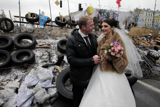 Newlyweds Mikhail and Margarita Nakonechniy share a tender moment in front of barricades on Independence Square, in a gesture of support for pro-Europe activists in Kiev, Ukraine, Saturday, Dec. 21, 2013.
