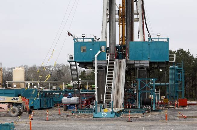 In this Dec. 23, 2013 photograph, Encana Corp., contractors work on a drilling rig in Amite County Supervisor Max Lawson's back pasture in Gillsburg, Miss. After a little more than two-years waiting to see if additional oil work would be done on a gravel pad, Lawson recalls the convoy of about 200 trucks bring the drilling rig and other gear to his property in late 2013.