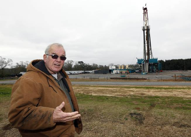 In this Monday, Dec. 23, 2013, photograph, Amite County Supervisor Max Lawson describes the convoy of about 200 trucks carting in a drilling rig and other gear on what was pasture land at his Gillsburg, Miss., farm. After a little more than a two-year wait, Encana Corp. contractors were finally drilling.