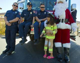 Operation FireH.E.A.T. (Holiday Emergency Assistance Team) firefighters enjoy a visit with Lupita Cambero, 10, and Santa on Christmas morning after delivering presents Wednesday, Dec. 25, 2013.