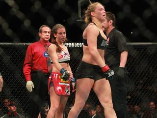 Miesha Tate extends her hand to shake Ronda Rousey's after Rousey submitted Tate with an arm bar to successfully defend her bantamweight title at UFC 168 Saturday, Dec. 28, 2013 at the MGM Grand Garden Arena.