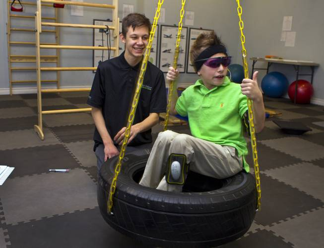 Sensory motor coach Cody Furin spins the tire swing for Christian Culotta, 9, as they work on physical and emotional stability at the Brain Balance Achievement Center on Monday, Dec. 30, 2013.