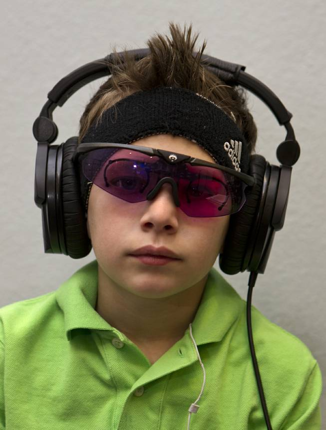 Christian Culotta, 9, wears high-tech glasses and headphones for visual and auditory stimulation at the Brain Balance Achievement Center on Monday, Dec. 30, 2013.
