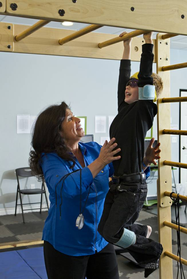 Dr. Susan DeVito steadies Chase Black, 7, as he hangs on the monkey bars for strength conditioning within the Brain Balance Achievement Center on Monday, Dec. 30, 2013.