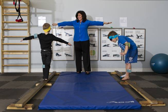 Dr. Susan DeVito coaches Chase Black, 7, and Cash Johnson, 7, on the balance beam within the Brain Balance Achievement Center on Monday, Dec. 30, 2013.