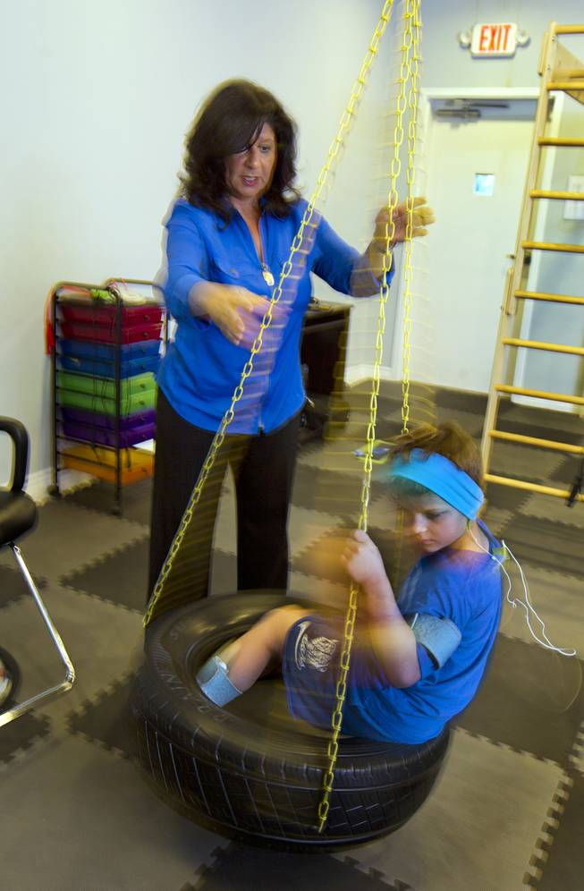Dr. Susan DeVito spins Cash Johnson, 7, on the tire swing for physical and emotional stability within the Brain Balance Achievement Center on Monday, Dec. 30, 2013.