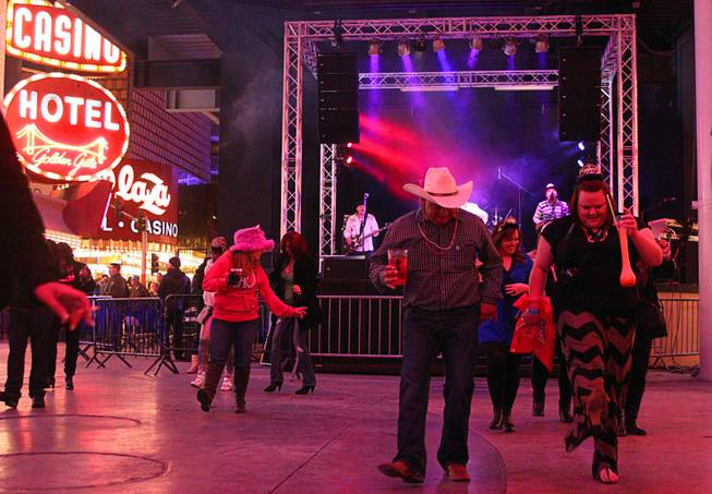 Partiers dance during New Year's Eve festivities at the Fremont Street Experience in downtown Las Vegas Tuesday, Dec. 31, 2013. An estimated 335,000 tourists were expected to visit Las Vegas to celebrate the new year.